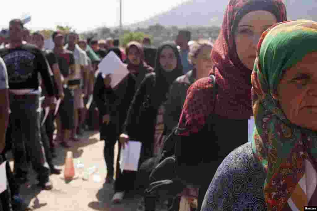 Para pengungsi dan migran mengantre di sebuah stadion sepakbola yang digunakan sebagai pusat pendaftaran di kota Mytilene, pulau Lesbos di Yunani (8/9). (Reuters/Dimitris Michalakis)