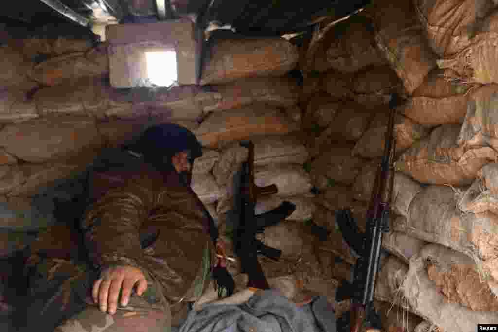 A rebel fighter rests with his weapons behind sandbags at insurgent-held al-Rashideen, Aleppo province, Syria, Dec. 30, 2016. ជនសកម្មប្រយុទ្ធរបស់ក្រុមឧទ្ទាមម្នាក់កំពុងសម្រាកនៅជិតកាំភ្លើងនៅខាងក្រោយបាវដីខ្សាច់ នៅតំបន់al-Rashideen ដែលកាន់កាប់ដោយពួកបះបោរ នៅក្នុងក្រុងAleppo។