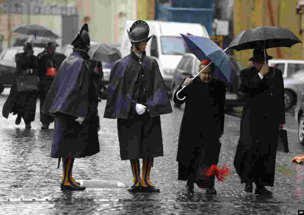 Cardinal Carlo Caffarra, second from right, and Cardinal Raymond Leo Burke, right, walk past two Swiss guards as they leave after a meeting at the Vatican, March 8, 2013.