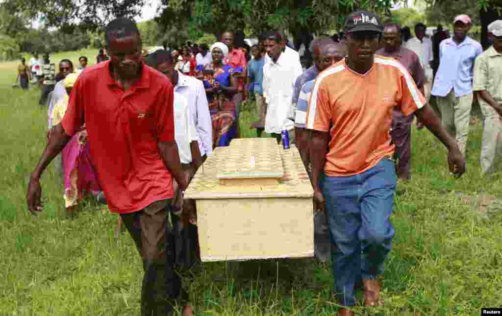 Pallbearers carry a coffin containing the remains of Francis Kamande killed when gunmen attacked the coastal Kenyan town of Mpeketoni, June 18, 2014.