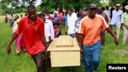 FILE - Pallbearers carry a coffin containing the remains of Francis Kamande killed when gunmen attacked the coastal Kenyan town of Mpeketoni, June 18, 2014.