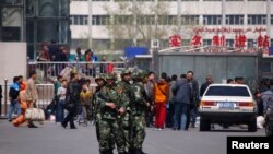Paramilitary policemen stand guard near the exit of the South Railway Station, where three people were killed and 79 wounded in a bomb and knife attack on Wednesday, in Urumqi, Xinjiang Uighur Autonomous region, May 1, 2014.