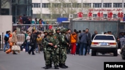 Paramilitary policemen stand guard near the exit of the South Railway Station, where three people were killed and 79 wounded in a bomb and knife attack in Urumqi, Xinjiang Uighur Autonomous region, May 1, 2014.