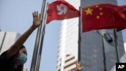 在香港和中國旗幟下香港抗議者伸出手掌表示五大訴求缺一不可。