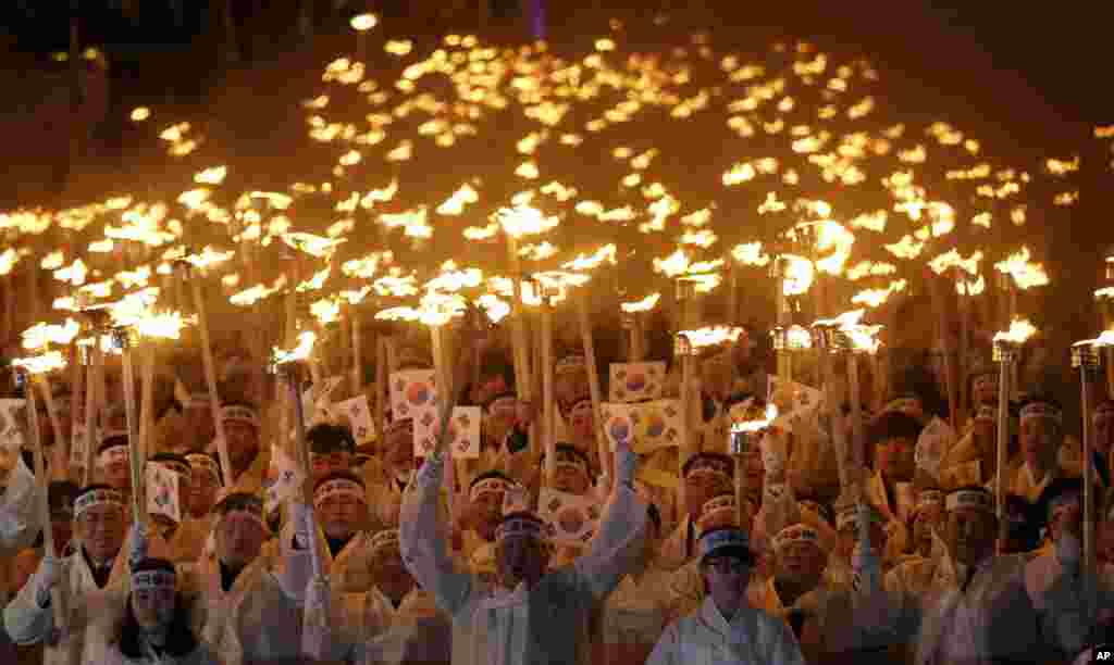 """在首尔以南的天安,穿着传统服装的韩国人举着火炬和国旗游行走过街头,庆祝""""三一节""""。这是纪念1919年3月1日韩国人发起反抗日本殖民统治的独立运动的周年日。"""