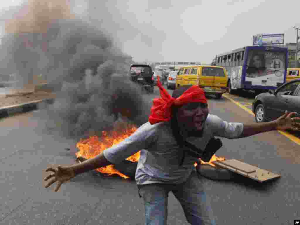A protester shouts slogans in front of a fire on a major road in Lagos on January 3, 2012. (AP)
