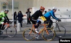 U.S. Secretary of State John Kerry, center, cycles past the Olympic Museum in Lausanne, France, March 16, 2015.