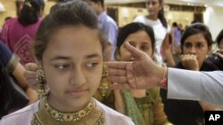 """People shop for gold jewelry in Ahmadabad, India, May 6, 2011, during the Hindu festival """" Akshay Tritiya"""", which is considered auspicious for buying gold. Indian-Americans' love affair with gold has made them targets for criminals."""
