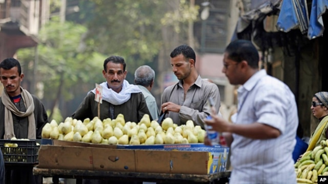 FILE - Egyptians buy fruits at a popular market in Cairo.