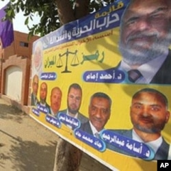 """A poster by Egypt's Muslim Brotherhood """"The Freedom and Justice Party'"""" outside a polling station in Cairo, November 28, 2011."""