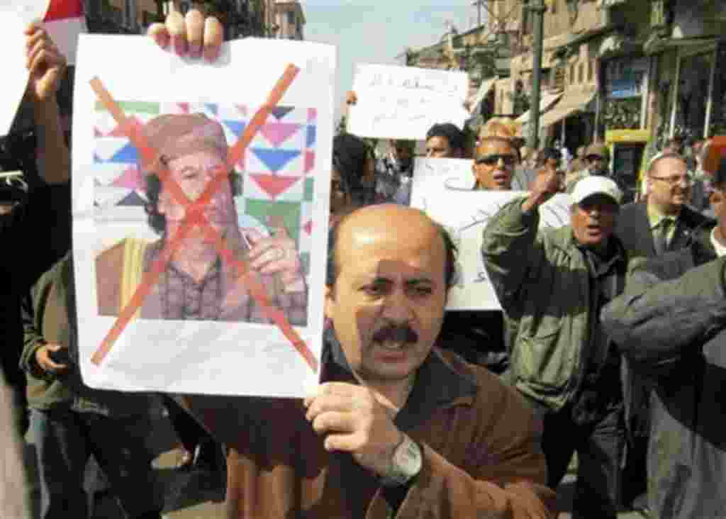 Protesters demonstrate against Libyan Leader Moammar Gadhafi, shown on placard at left, in the Mediterranean port city of Alexandria in Egypt, February 20, 2011