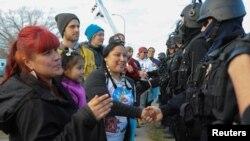 Para pengunjuk rasa di negara bagian North Dakota berbincang dengan polisi setempat (15/11).
