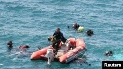 Một thợ lặn vớt một bé gái lên thuyền cứu hộ trong lúc các thợ lặn khác tìm kiếm các nạn nhân ngoài khơi vùng biển phía tây Thổ Nhĩ Kỳ, ngày 6/9/2012