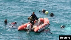 A diver from the Turkish sea police (C) carries a girl in a rescue boat as other divers look for victims in the Aegean sea off Menderes, western Turkey, September 6, 2012.