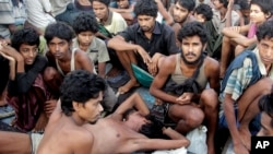 FILE - In this May 20, 2015, file photo, migrants including Myanmar's Rohingya Muslims sit on the deck of their boat as they wait to be rescued by Acehnese fishermen on the sea off East Aceh, Indonesia. Myanmar called sad and regrettable a move by the United States to place the country on a list of the world's worst human trafficking offenders, while rights groups welcome it as long overdue.