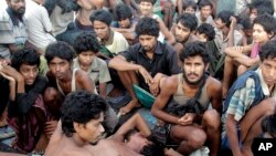 FILE - In this May 20, 2015, file photo, migrants including Myanmar's Rohingya Muslims sit on the deck of their boat as they wait to be rescued by Acehnese fishermen on the sea off East Aceh, Indonesia. Myanmar called sad and regrettable a move by the Uni