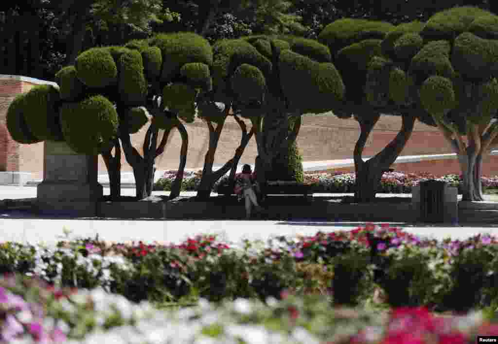 A woman listens to music as she sits on a bench during a hot summer day at Madrid's El Retiro park, Spain.