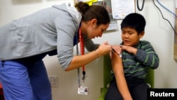 A boy gets an influenza vaccine injection at a health care clinic, in Boston, Massachusetts, in this January 12, 2013, file photo.