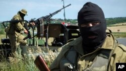 Pro-Russian fighters stand patrol near Luhansk, eastern Ukraine, July 2, 2014.