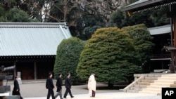 Japanese Prime Minister Shinzo Abe follows a Shinto priest to pay respect for the war dead at Yasukuni Shrine in Tokyo, Dec. 26, 2013.