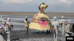 Warga setempat melarung ogoh-ogoh ke kolam penampungan lumpur, menandai peringatan delapan tahun musibah lumpur Lapindo, Kamis, 29 Mei 2014 (Foto: VOA/Petrus Riski)