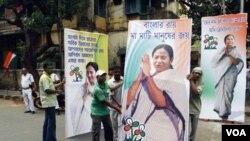 Pendukung partai Kongres memasang gambar Mamata Banerjee di Kolkata (13/5). Partai Kongres menang 215 kursi dari 294 kursi yang diperebutkan di Benggala barat, menyingkitkan dominasi partai Komunis.