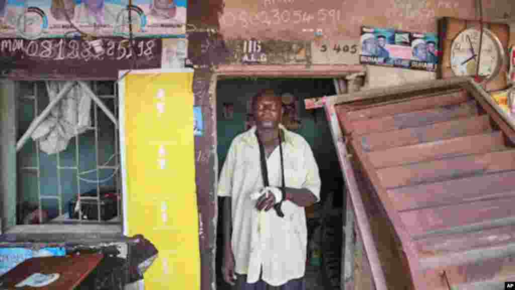 Yushau Ibrahim, stands outside his shop with an injured arm after security force raided and stole nearly $10,000 at Katangua market in Lagos.