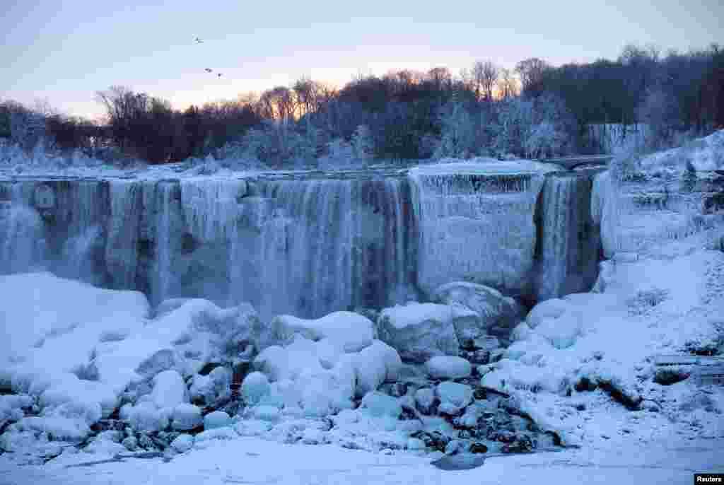 """从加拿大的安大略省尼亚加拉市看尼亚加拉大瀑布中的美国瀑布,一群鸟飞过天空,天寒地冻中并非""""千山鸟飞绝,万径人踪灭""""。"""