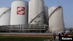 FILE - Officials walk by palm oil storage tanks at Indonesia's Sinar Mas Agro Resources refinery May 3, 2012