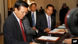 Cambodia National Rescue Party's Vice President Kem Sokha, left, registers before a meeting at at National Assembly, in Phnom Penh, Cambodia, Friday, Aug. 8, 2014. Lawmakers from opposition Cambodia National Rescue Party on Friday appeared for the first time at the meeting of National Assembly, ending their ten months of boycott of parliament over claims that the results of the July 2013 general election were rigged. (AP Photo/Heng Sinith)