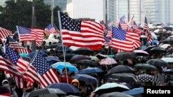 Para pengunjuk rasa anti-pemerintah melambaikan bendera AS saat demonstrasi di Hong Kong, China, 15 September 2019. (Foto: Jorge Silva/ Reuter)