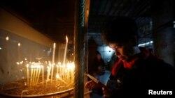 Un visiteur allume une bougie à l'intérieur de l'Église de la Nativité pour Noël à Bethléem, le 25 décembre 2016.