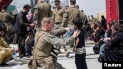 کابل ایئر پورٹ پر ایک امریکی فوجی افغان بچے کو پانی پلا رہا ہے۔