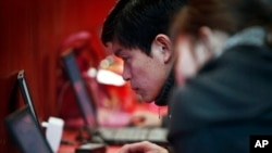 FILE - A man uses the free internet service at a commercial expo in Beijing, Feb. 26, 2011.