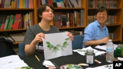 Undergraduate student Moe Lewis, left, shows her watercolor painting of peony leaves at a traditional Chinese painting class at the Confucius Institute at George Mason University in Fairfax, Va., on May 2, 2018.