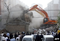 FILE - Chinese police and officials stand by as illegally-built houses are demolished in Changchun, northeast China's Jilin province, July 5, 2008.