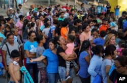 """Migrants, many who were returned to Mexico under the Trump administration's """"Remain in Mexico,"""" program wait in line to get a meal in an encampment near the Gateway International Bridge in Matamoros, Aug. 30, 2019."""