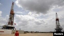 Un trabajador de un campo petrolero camina junto a las plataformas de perforación en un pozo de petróleo operado por la petrolera estatal de Venezuela PDVSA, en el rico cinturón petrolero del Orinoco, el 16 de abril de 2015.