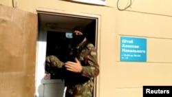 Një polic i maskuar gjatë bastisjes në një zyrë lokale të kritikut të Kremlinit, Alexei Navalny, në qytetin Perm të Rusisë, 12 shtator 2019