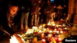 Seorang perempuan meletakkan lilin di sinagoge di mana dua orang terbunuh dalam penembakan di Halle, Jermani, 10 Oktober 2019.