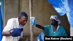 Un agent de santé mesure la température d'un homme entrant dans le centre de traitement Ebola à Beni, en République démocratique du Congo, le 1er avril 2019.