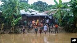 Rohingya refugees look at floodwater following heavy rains at the Rohingya refugee camp in Kutupalong, Bangladesh, July 28, 2021.
