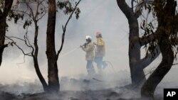 Petugas pemadam kebakaran mengendalikan titik api di dekat Bredbo, selatan Ibu Kota Australia, Canberra, 2 Februari 2020. Pemuda Indonesia, Tjia Johan Setiawan, menjuarai kompetisi global yang bertujuan mendeteksi persebaran api dalam kebakaran hutan. (Foto: AP)