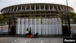 Pedestrians wearing protective masks, following the coronavirus disease (COVID-19) outbreak, walk in front of the National Stadium, the main stadium of Tokyo 2020 Olympics and Paralympics in Tokyo, Japan, July 7, 2021.