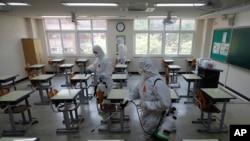 한국 서울의 한 고등학교에서 신종 바이러스 감염증(COVID-19) 방역 관계자들이 교실 내 방역작업을 하고 있다.