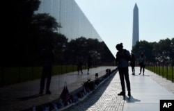 FILE - With the Washington Monument in the background, people visit the Vietnam Memorial in Washington on May 27, 2016, on the start of the Memorial Day weekend.