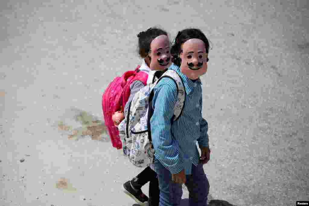 Palestinian students wearing masks return from school in Tubas, Israeli-occupied West Bank.