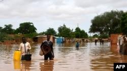 Des gens, portant leurs effets personnels, marchent dans une rue inondée du quartier Kirkissoye à Niamey, au Niger, le 27 août 2020.
