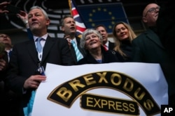 British MEPs, or Member of the European Parliament, celebrate as they march out of European Parliament with their luggage in Brussels to take the Eurostar train back to Britain, Jan. 31, 2020, the day the U.K. is due to leave the EU.
