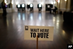 FILE - A sign is displayed for voters to guide the way at a precinct during Georgia's Senate runoff elections on Jan. 5, 2021, in Atlanta.